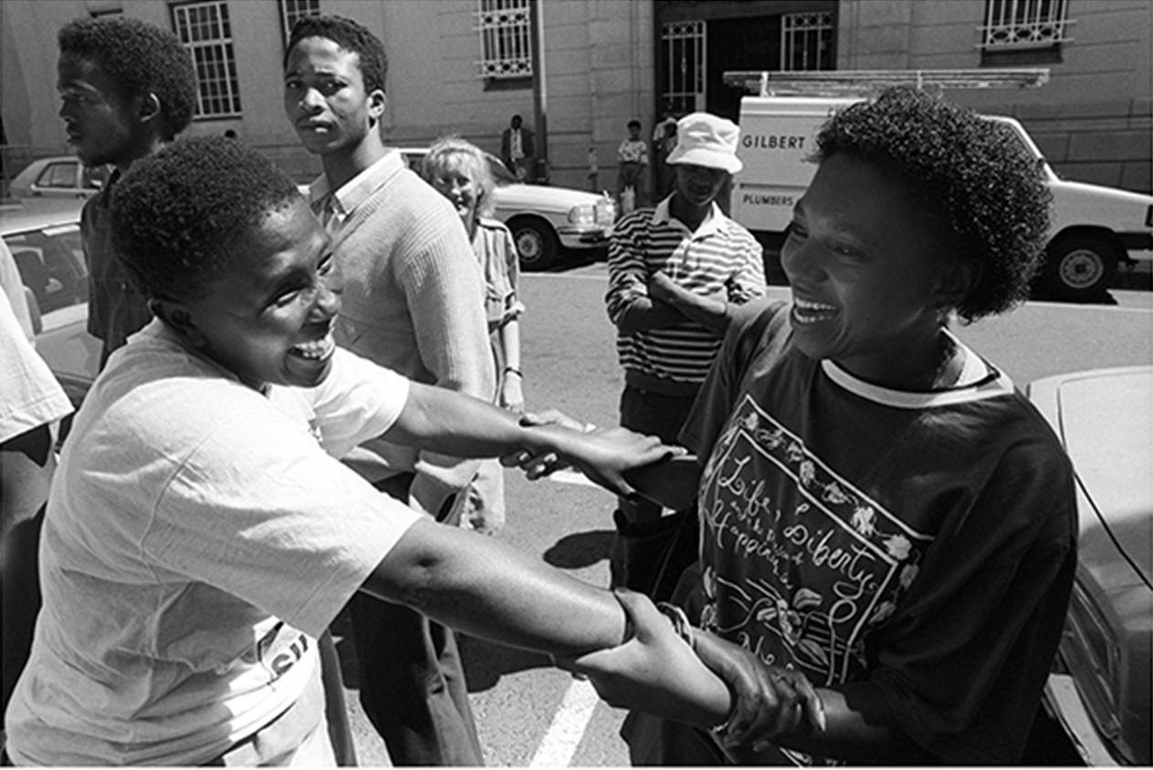 'Grassroots' journalist Veliswa Mhauli greets comrades outside Cape Town Magistrates Court after release from Section 29